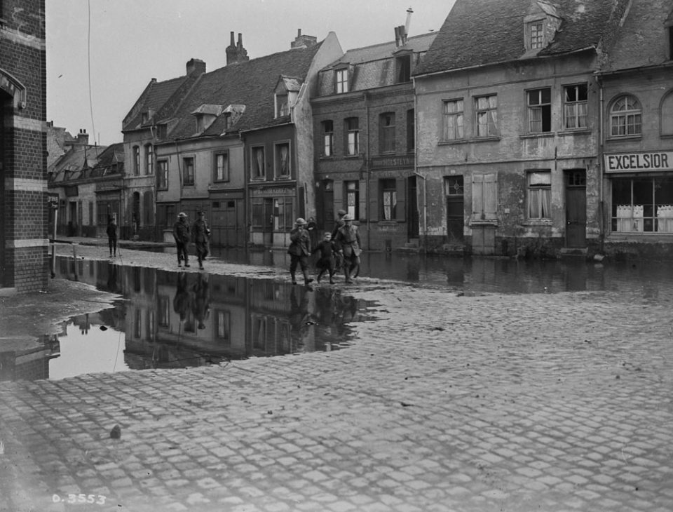 Canadians escorting a French girl through the flooded streets of Valenciennes (LAC M#3397417).