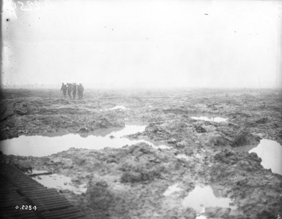 Bringing in a wounded soldier upon a stretcher at Passchendaele (LAC M#3395863).