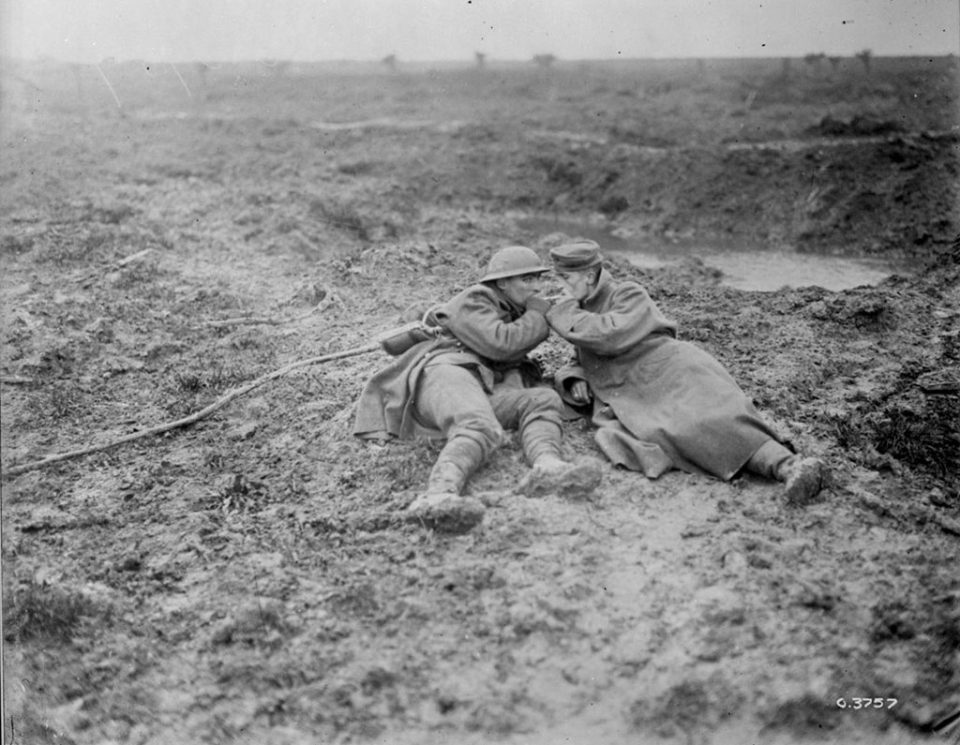 A wounded Canadian and a wounded German soldier share a light (LAC M#3397047).