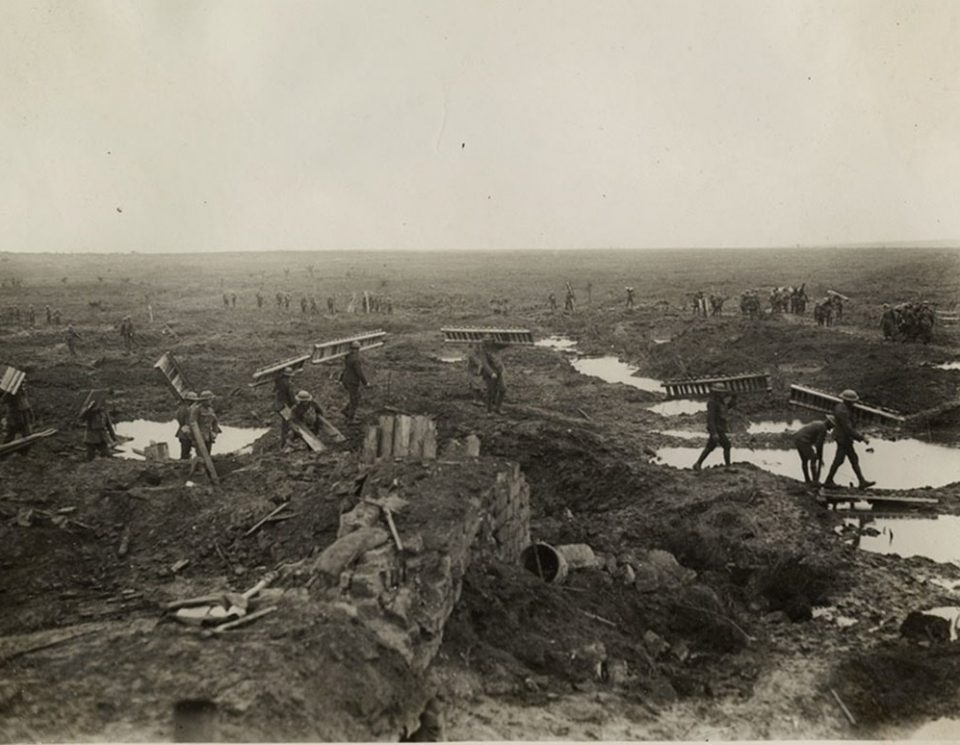 Canadians carrying trench mats at Passchendaele. Wounded german prisoners with Canucks in the background (LAC M#3623660).